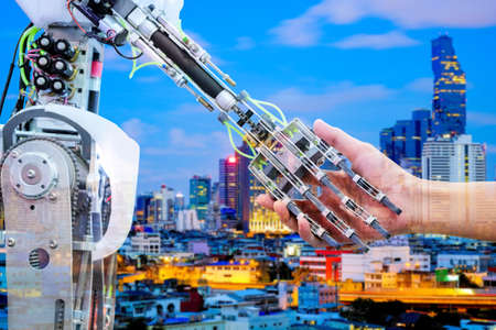 AI Robot handshake with human for ่join on teamwork on blurred building construction on blue tone color background, industry 4.0 and business construction concept, double exposure image