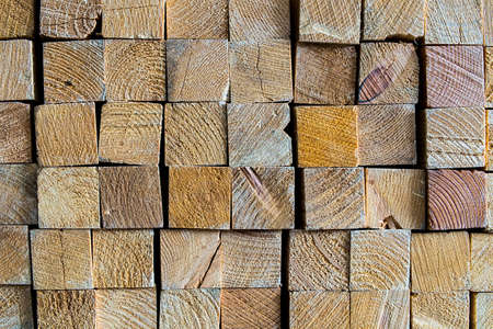 Industrial heads wood of of sawed timber material that are stacked in a square on wood warehouse store, wood texture and background