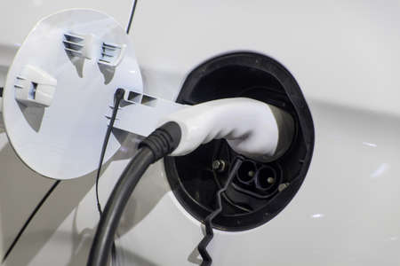 Close-up gripping of electric charge machine connected with plug for charging battery on white smart car (EV Car), Electric power is an alternative fuel for smart vehicles, eco energy