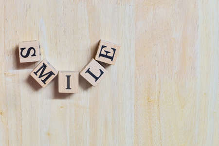Smile concept idea, wooden letters connect is curve to message on wooden desk, informative and communication about happy, close-up on top-view and copy space