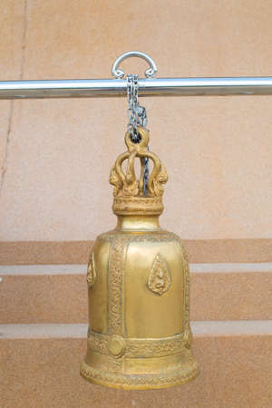 reverberate: ancient bell gold color in Thailand temple.