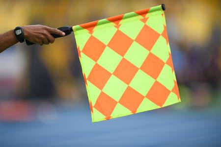 Assistant referee hold flag , offside signal Stock Photo