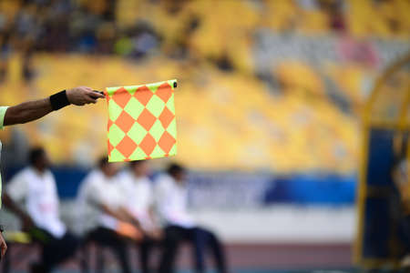 Assistant referee hold flag,offside signal Stock Photo