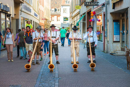 alphorn: Alphorn player in traditional Bavarian costumes performing on the street of Heidelberg at the fall folkfestival - September 24 2016, Heidelberg, Germany