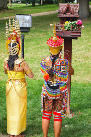Two Thai women in colorful traditional Thai costumes during praying outdoors at the Thai festival Amazing Thailand in Bad Homburg. Bad Homburg, Germany - July 31 2016