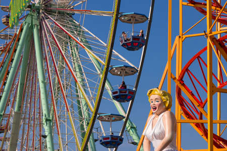 Closeup of a big observation wheel in the amusement park with the figure of Marilyn Monroe in the foreground. Bad Duerkheim, Germany - September 10 2016th