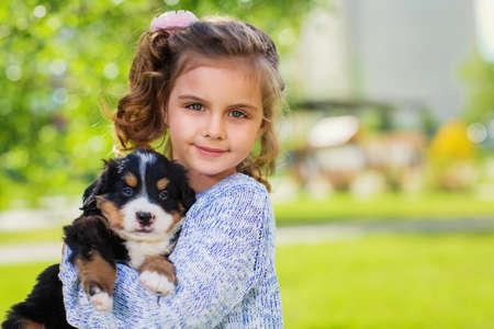 Little girl with a berner sennenhund puppy, outdoor, summer Stock Photo