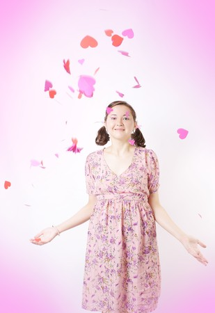 Young beautiful girl threw paper hearts photo