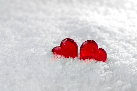 Two red hearts lie on the white fluffy snow in winter. Symbol of love. Valentine's day