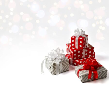 Surprise gifts for new year, Christmas, birthday. Red polka dot box with big bow on white background with bokeh