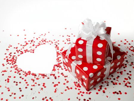 Surprise gift for New Year, Christmas, Birthday, loved ones. Red polka dot box with white bow on white background with confetti. heart. the view from the top