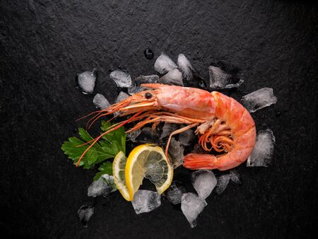 one shrimp on a stone black table with lemon, parsley leaves and ice