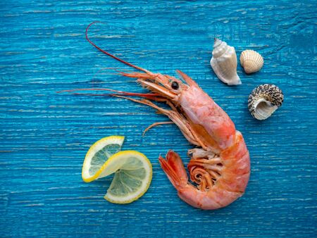 one shrimp and lemon on an old blue wooden table
