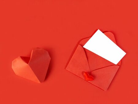 Red paper envelope with a note for Valentines Day on a white background with hearts