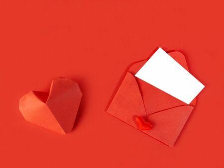 Rode papieren envelop met een briefje voor Valentijnsdag op een witte achtergrond met hartjes