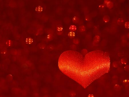 Red heart on a blurry red background with bokeh. defocus. Symbol of love. Valentines day , birthday, gift. 版權商用圖片