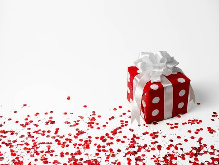gift for New Year, Christmas, Birthday, loved ones. Red polka dot box with white bow on white background with confetti. Stock Photo