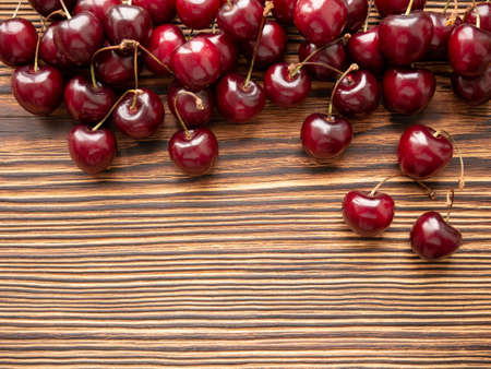 Sweet cherry on a wooden background. Close-up, copy space