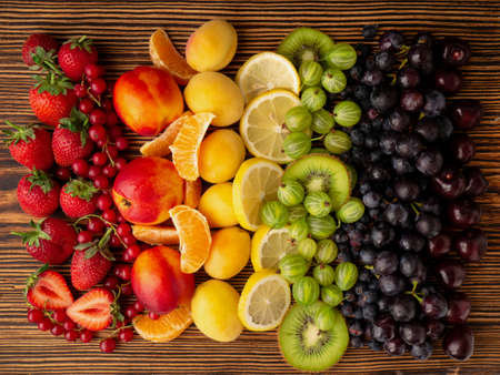 Fresh berries and fruit on a wooden background. Rainbow color. the concept of healthy eating. The view from the top