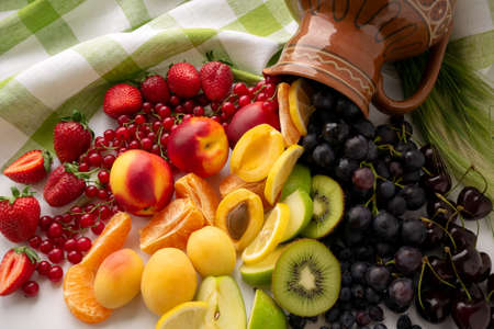 A colored rainbow of berries and fruit spilled out of the jug. The concept of healthy eating. Top view