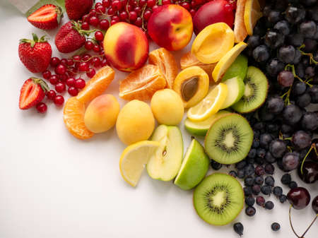 A scattering of fresh, ripe berries and fruits of different colors. Top view.