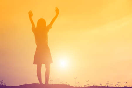 Silhouette of woman praying over beautiful sky background Stock Photo