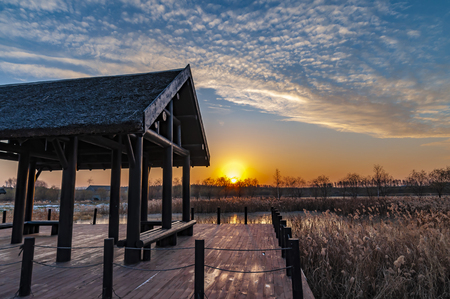 Wooden pavilion and winter sunset at North Lake National Wetland Park, Changchun, China