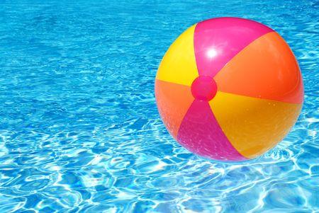 Een kleurrijke strand bal zwevend over het zwembad Stockfoto