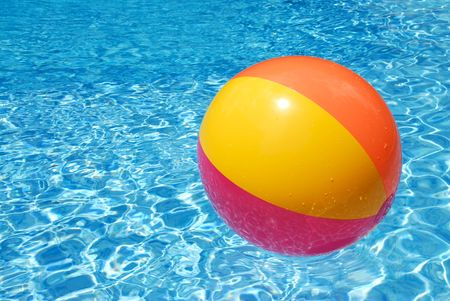 pool ball: A colorful beach ball floating on the  swimming pool