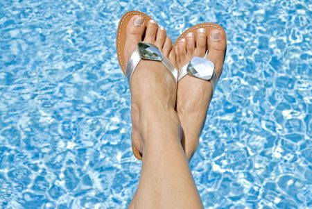 flipflop: Females Feet Wearing Silver Flipflop over the Swimming Pool
