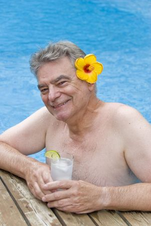 Mature Man Holding a Glass of Gin and Tonic in a Swimming Pool