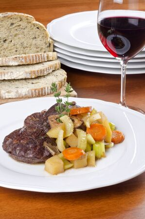 Slow Cooked Beef Shank Served with Bread and Red Wine photo