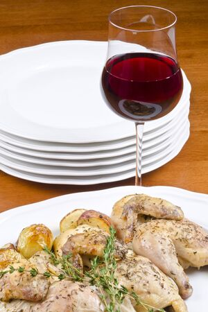 Roasted Cornish Game Hen and  Potatoes Served with Red Wine photo