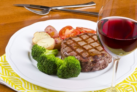 Beef Rib Eye Steak Served with Vegetables and Red Wine photo