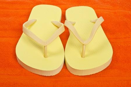 flops: Yellow Flip Flops on Orange Color Towel Stock Photo