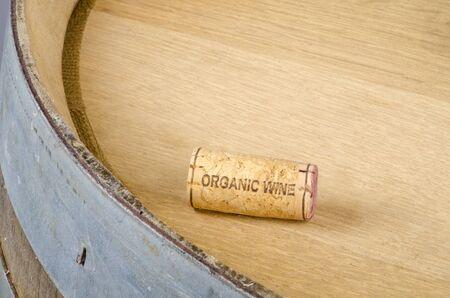 Cork Labelled Organic Wine on Top of an Oak Barrel