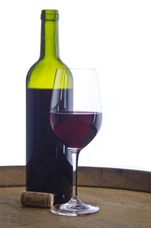 Glas rode wijn en een fles rode wijn op de top van een eiken vat Stockfoto