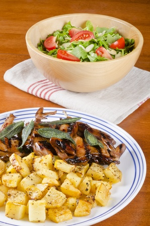 Barbecued Quails Served with Roasted Rutabaga and a Bowl of Arugula Salad Imagens