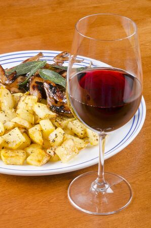 barbecued: Barbecued Quails Served with Roasted Rutabaga and a Glass of Red Wine Stock Photo