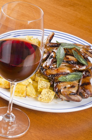 rutabaga: Barbecued Quails Served with Roasted Rutabaga and a Glass of Red Wine Stock Photo