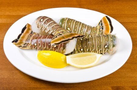 marine crustaceans: Lobster Tails and Lemon Wedges on a Plate
