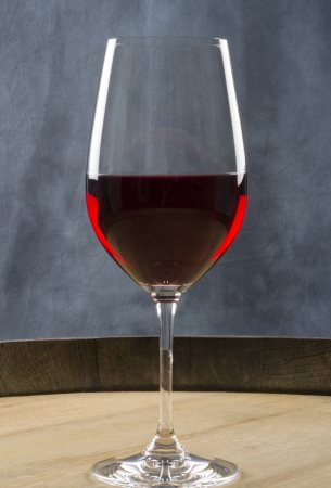 Glass of Red Wine on Top of a Wine Barrel Banco de Imagens
