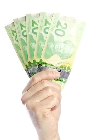 mano con dinero: Mano que sostiene billetes de veinte D�lar canadiense