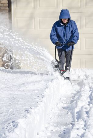 snow clearing: Man Using Snow Blower to Clear His Driveway