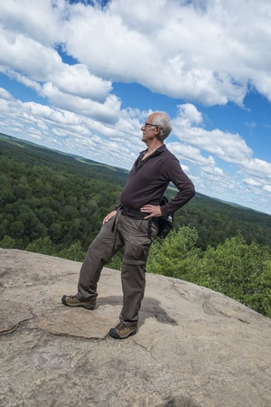 rugged terrain: Mature Man Standing on Top of a Cliff
