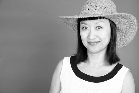 前髪と帽子とアジアの女性の黒と白のスタジオ ポートレート