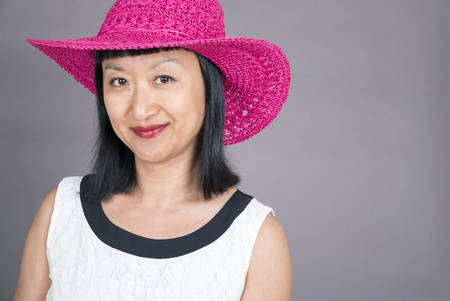 Studio Portrait of an Asian Woman with Bangs and Fuschia Straw Hat Banco de Imagens