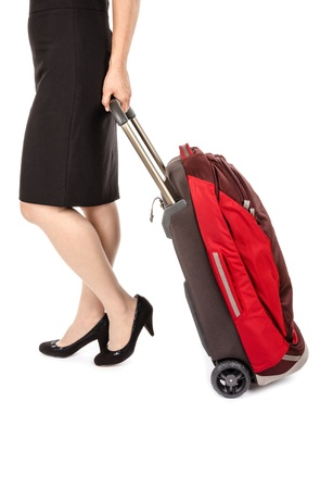 pencil skirt: Woman Wearing Black Pencil Skirt and Pumps Pulling a Small Travel Luggage