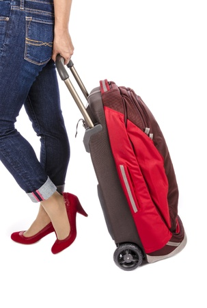 capri pants: Woman Wearing Capri Blue Jeans and Suede Red Pumps Pulling a Small Travel Luggage