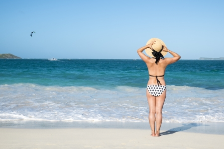 Woman with Polka Dot Bikini Looking Out to the Caribbean Sea  Stock Photo - 24736537